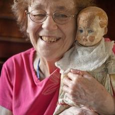 Aili Rajavaaralla on sylissään hänen elämänsä ensimmäinen nukke, joka oli mukana jo evakkomatkalla. Sen voi muistaa ja siitä voi tykätä, vaikka lähimuistia ei enää olisikaan. Kuva: Marja Söderlund